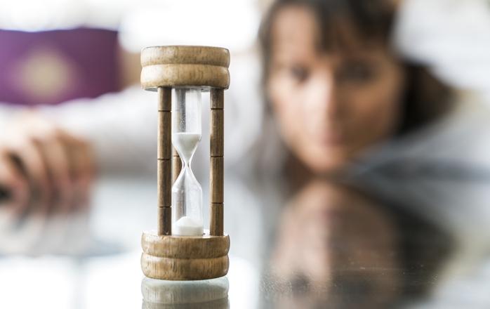woman viewing hourglass, aging